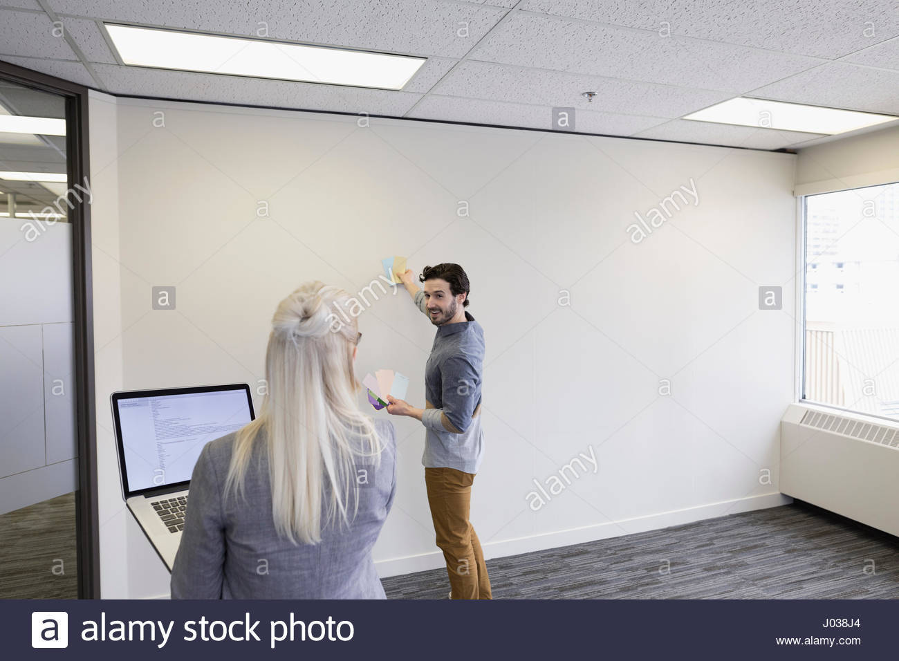 Business People Viewing Paint Swatches On Wall In Empty New Office