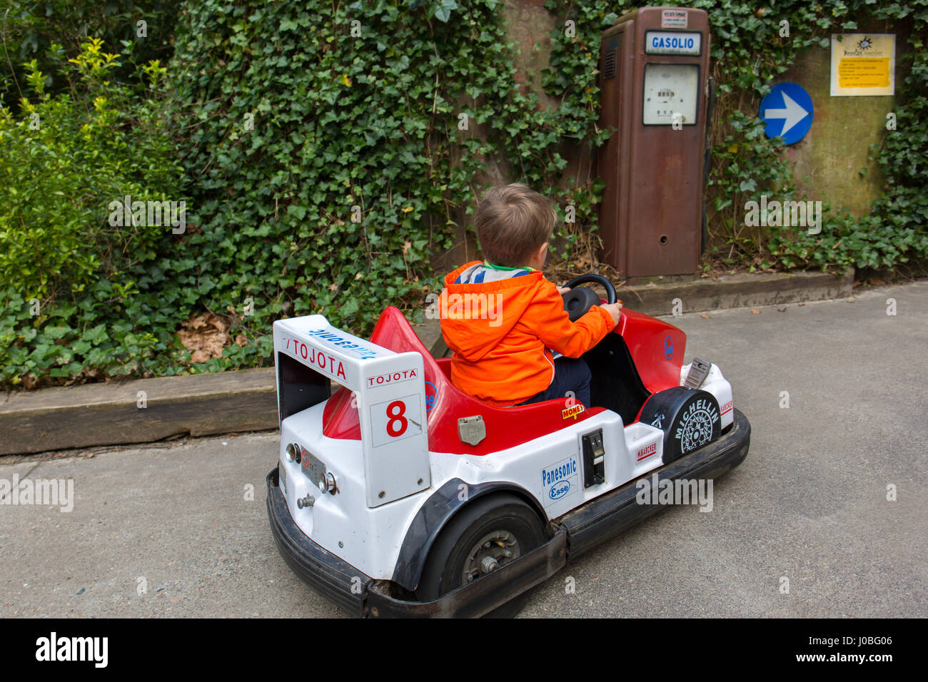 a kid little boy toddler driving an electric toy car and pulling into a gas station