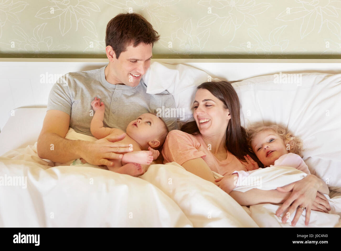 Baby bed with parents - Baby Girl And Toddler Sister Huddled In Bed With Parents