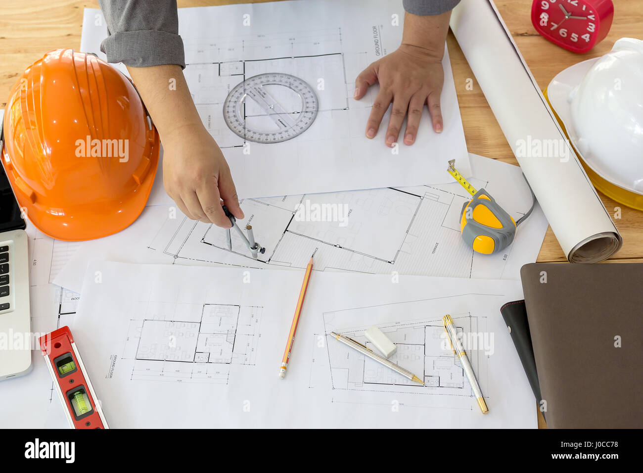 Architect working on blueprint architects workplace architect working on blueprint architects workplace architectural project blueprints ruler calculator laptop and divider compass construction malvernweather Gallery