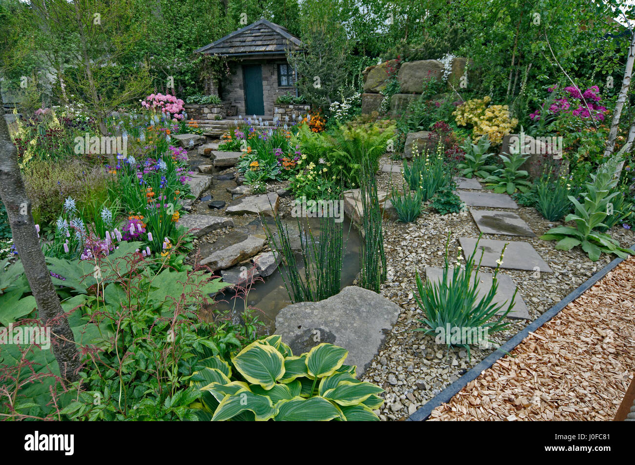 Country cottage garden - A Country Cottage Garden In A Wooded Rockery With Colourful Planting Stock Photo