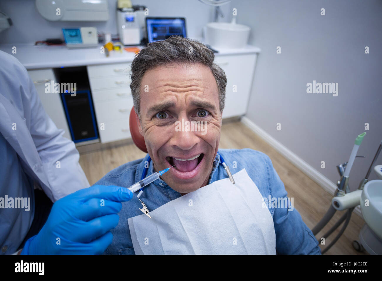 Dentist Injecting Anesthetics In Scared Male Patient Mouth At Dental Clinic
