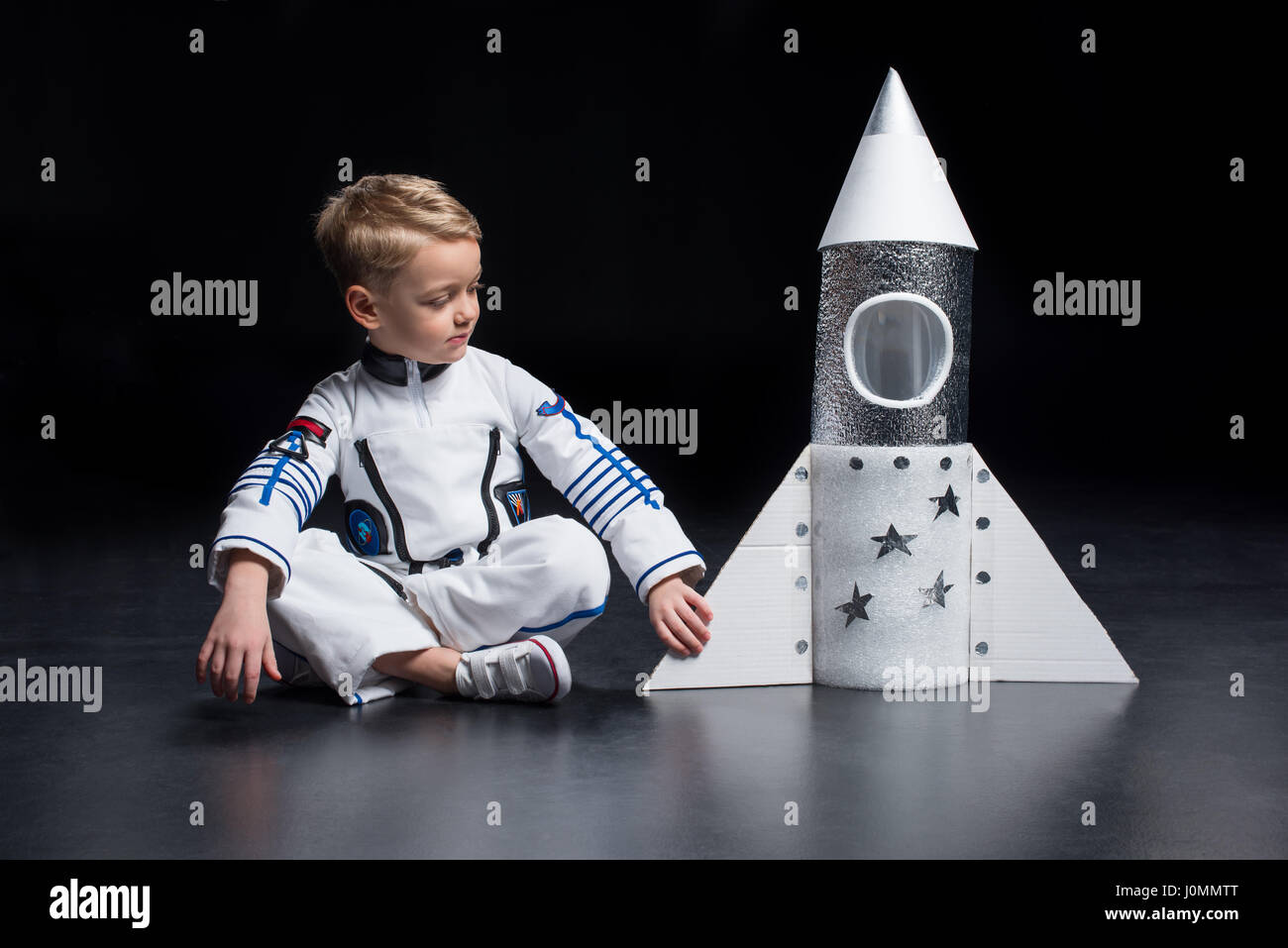 Little Boy Astronaut In Space Suit Sitting And Looking At Toy Spaceship