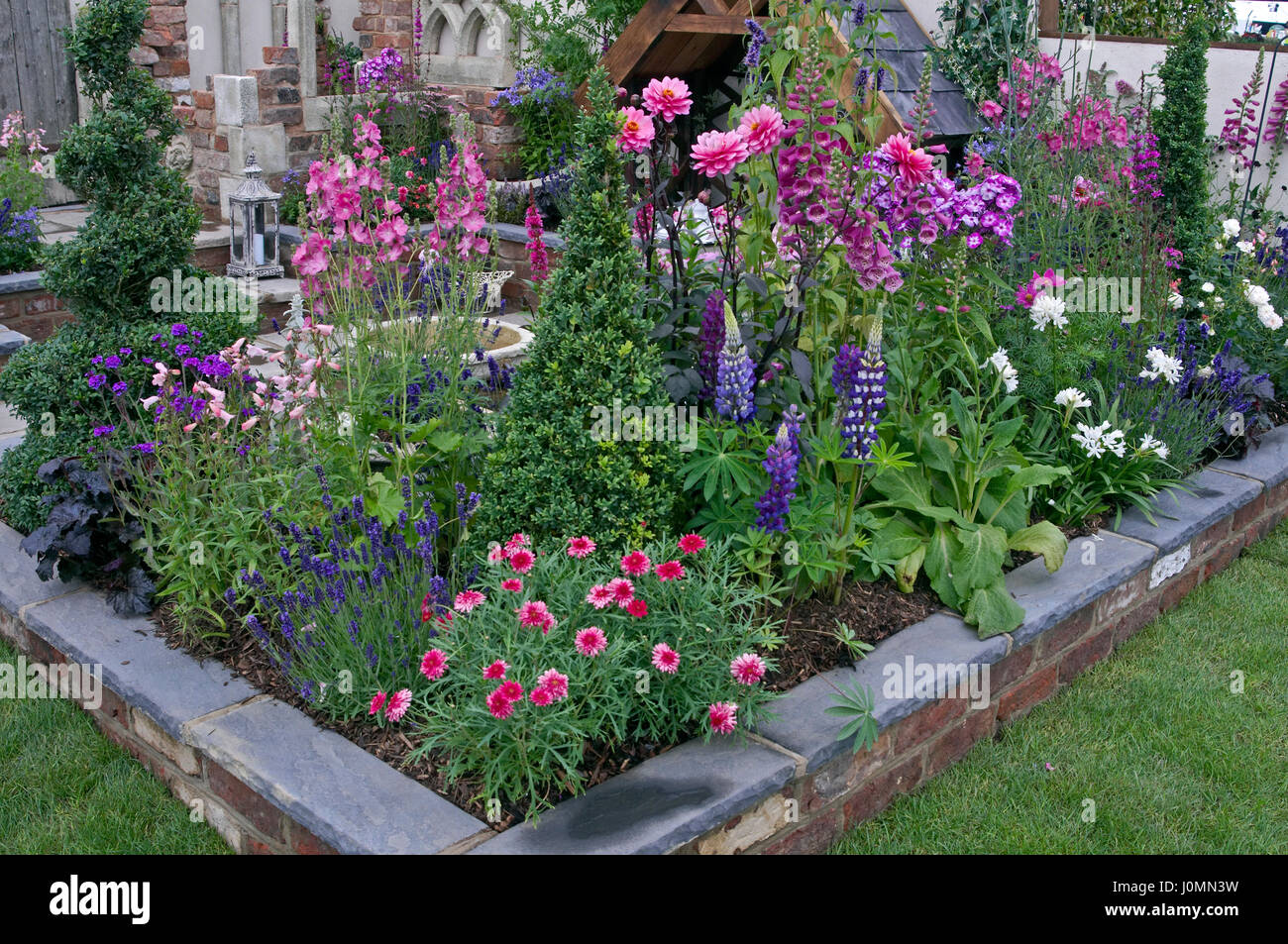 colourful planting in a raised flower bed of a patio garden stock
