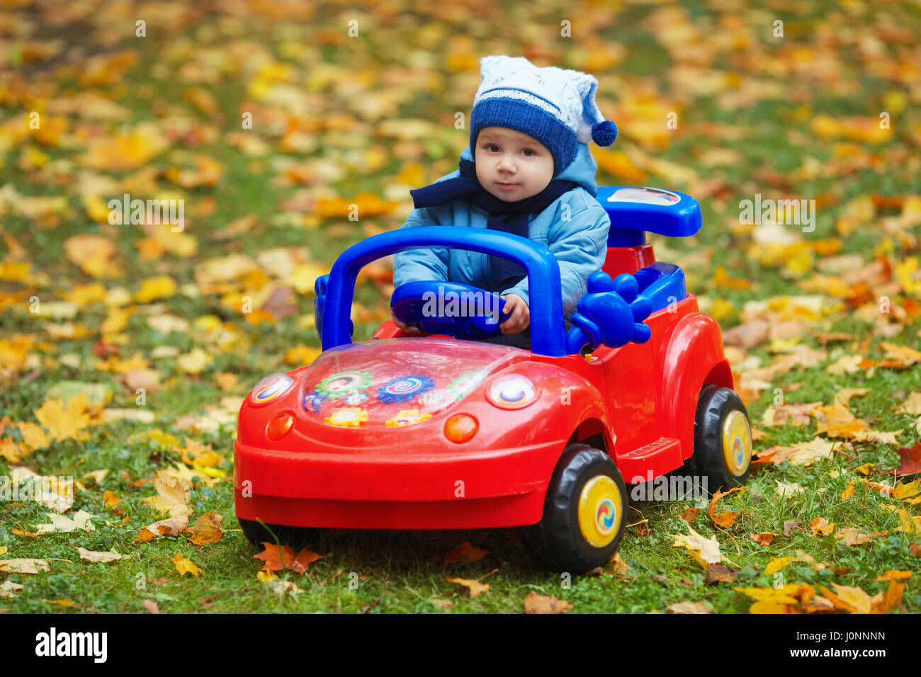 Little Boy With Toy Car : Little funny boy driving toy car stock photo