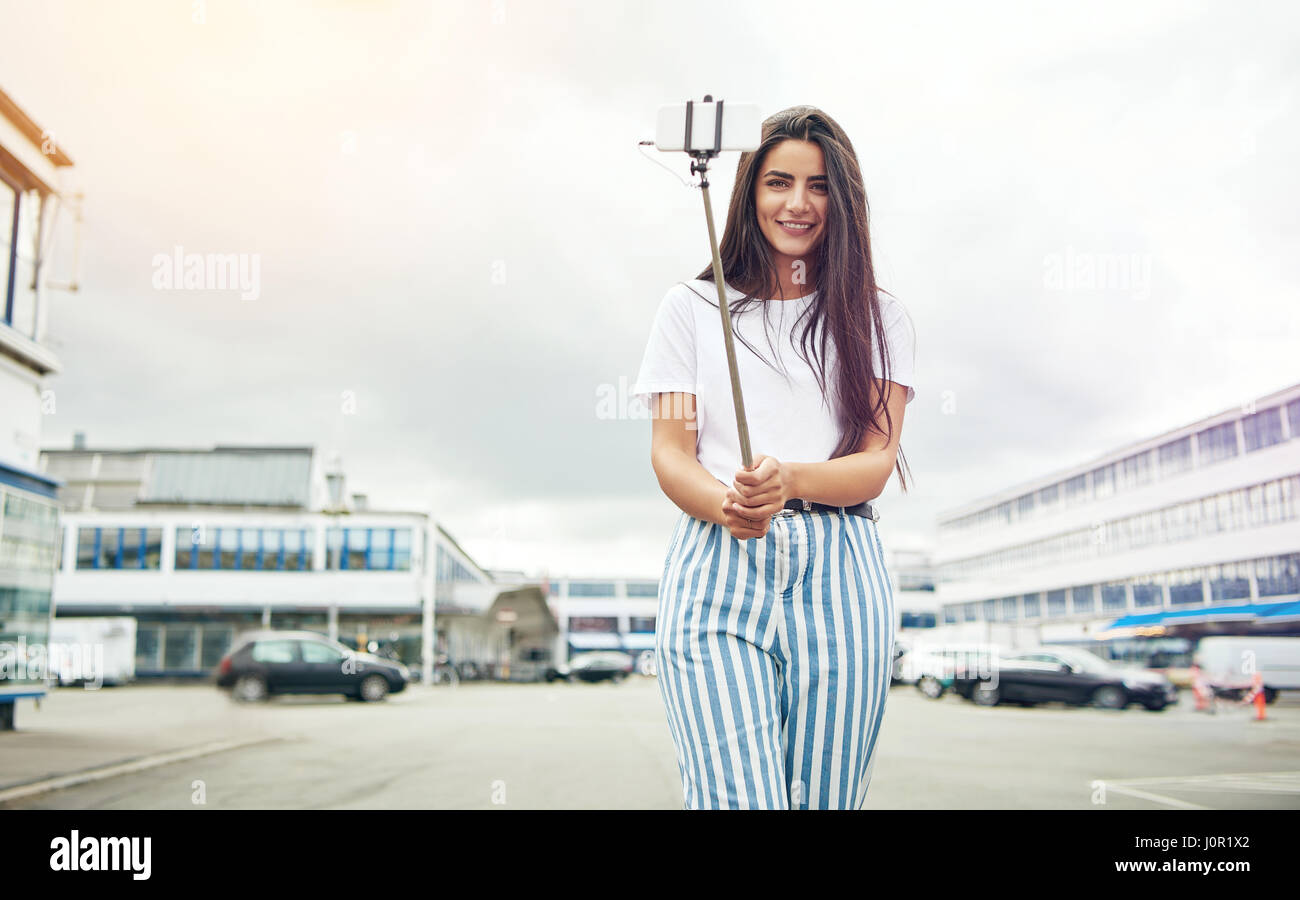 Stock Photo - Wide angle view of grinning beautiful woman taking her own  picture with camera