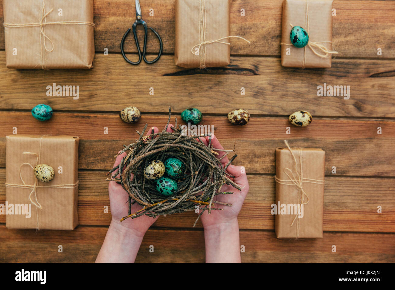 Wrapped gifts and girls hands holding a nest with easter eggs stock wrapped gifts and girls hands holding a nest with easter eggs negle Image collections
