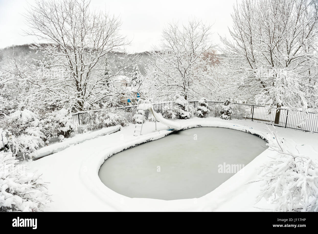 backyard swimming pool in winter after heavy snow fall storm