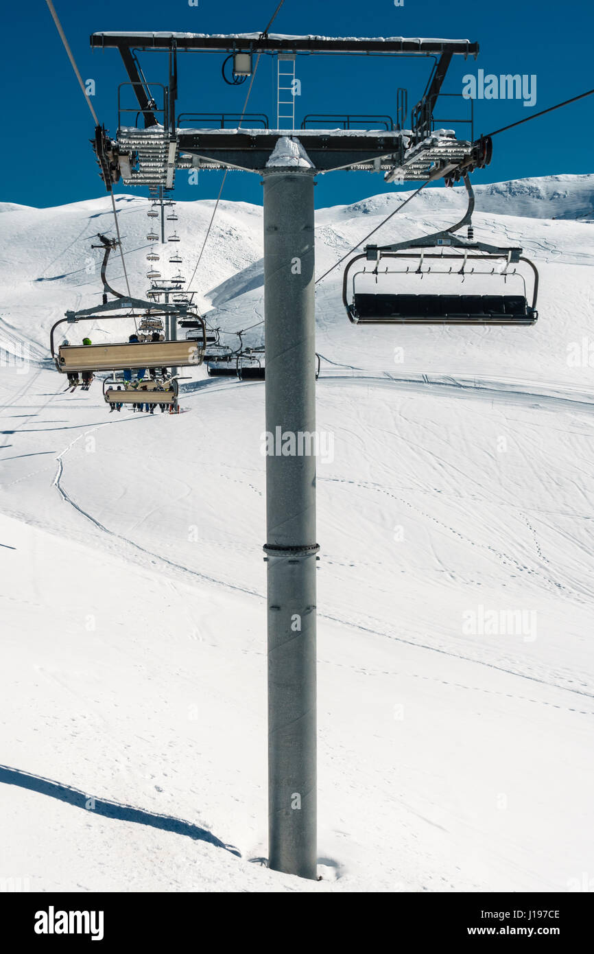 Ski lift pillar with seats going over the sunny mountain with ...