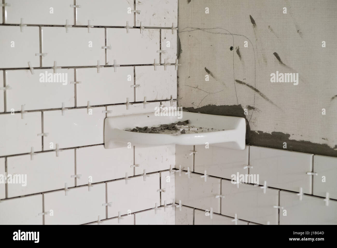 stock photo tub surround for a tall shower with white subways tiles set vertically on cement backer board during a major home renovation