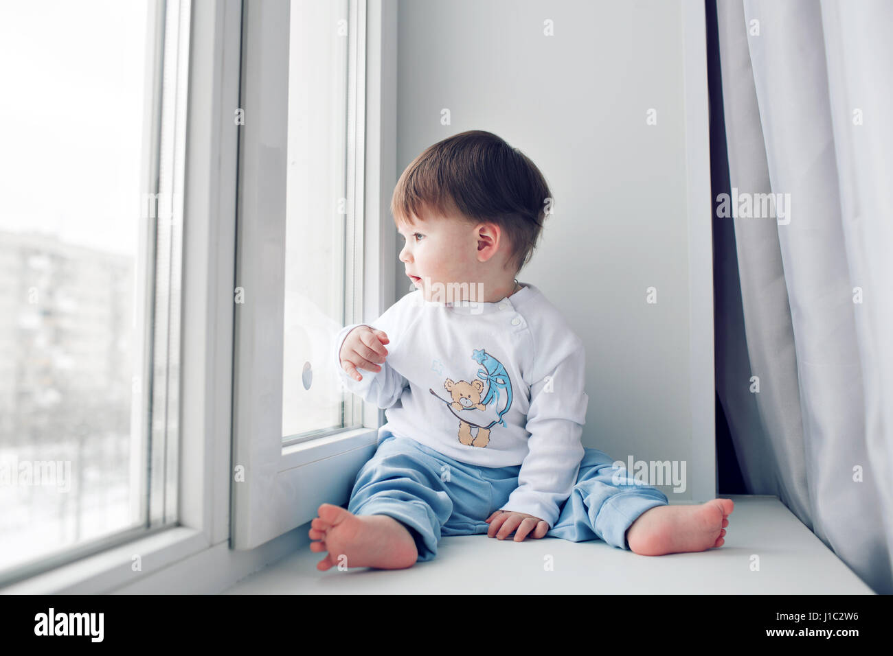 Adorable little baby seating on windowsill. looking out the window ...