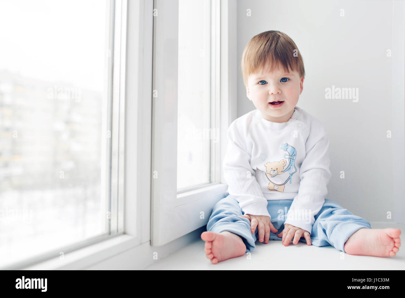Adorable little baby seating on windowsill. look at the camera ...