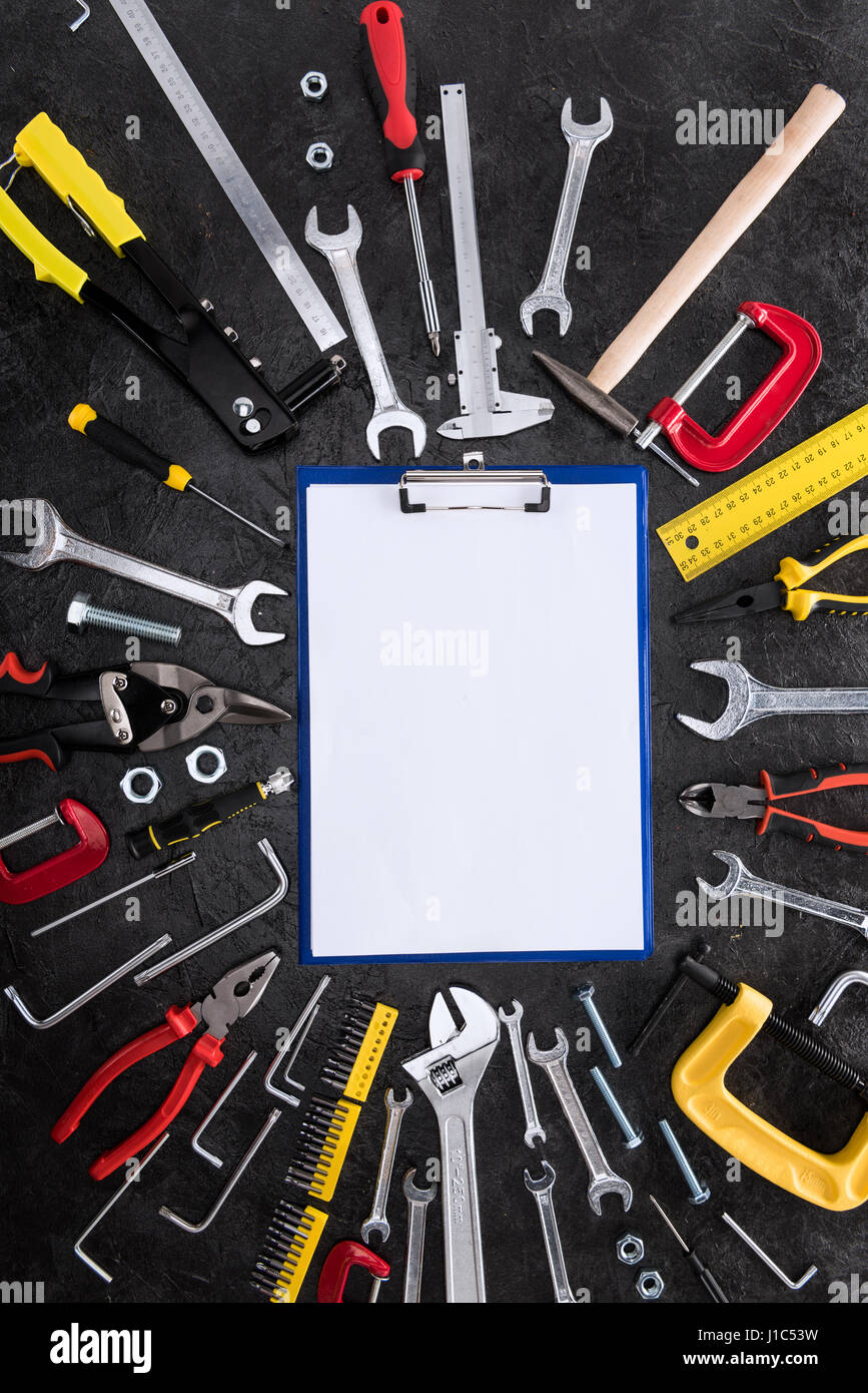 top view of set of construction tools and blank clipboard stock