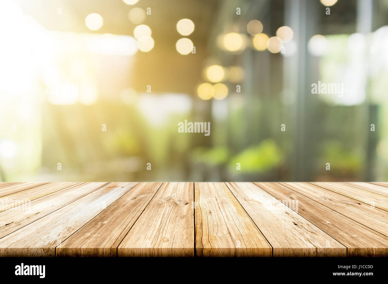Empty light wood table top with blurred in coffee shop background