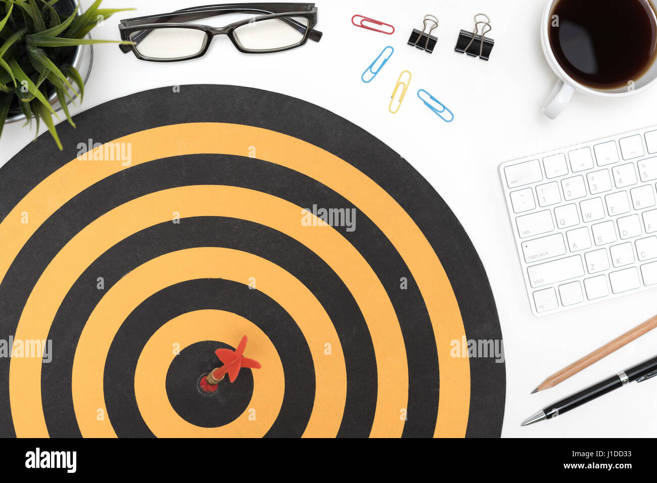 Dart Target Arrow Hitting On Bullseye In Dartboard Over Office Desk Table  Background With Eye Glasses, Pen, Pencil, Computer And Cup Of Coffee