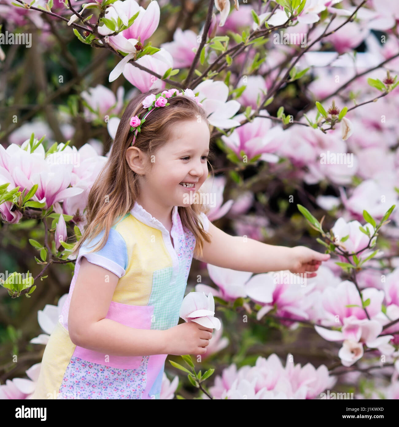 Happy little girl in pastel color dress and flower crown playing happy little girl in pastel color dress and flower crown playing under pink magnolia tree picking big flowers in blooming spring garden child with ma izmirmasajfo Gallery