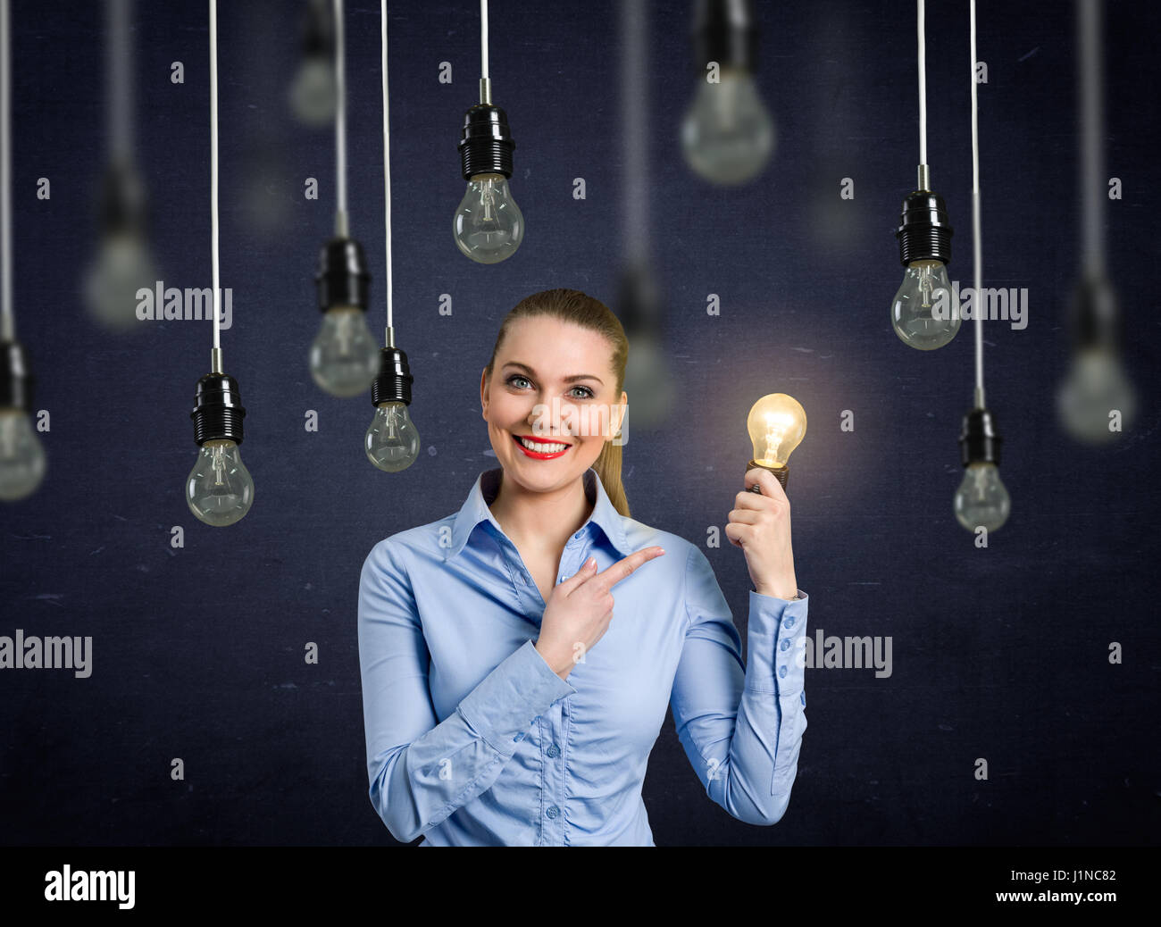 Woman holding light bulb above head as a sign of new idea Stock ... for Girl Holding Lamp  579cpg