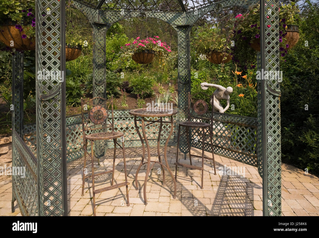 bistro style table and chairs inside a gazebo in a landscaped