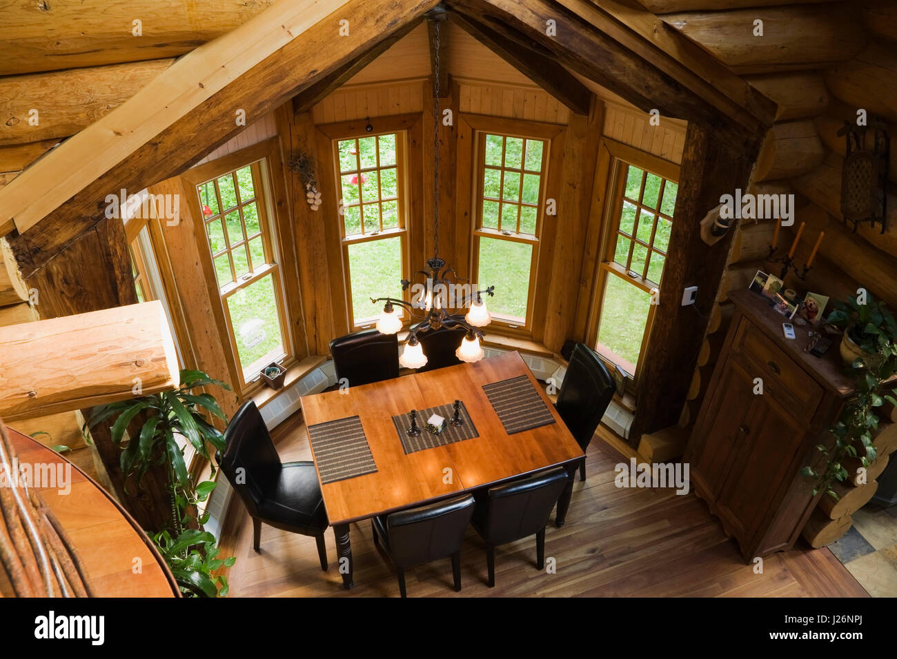 View From Mezzanine Of The Wooden Dining Table With Leather Chairs In Room Inside A 2003 Built Cottage Style Residential Log Home Quebec