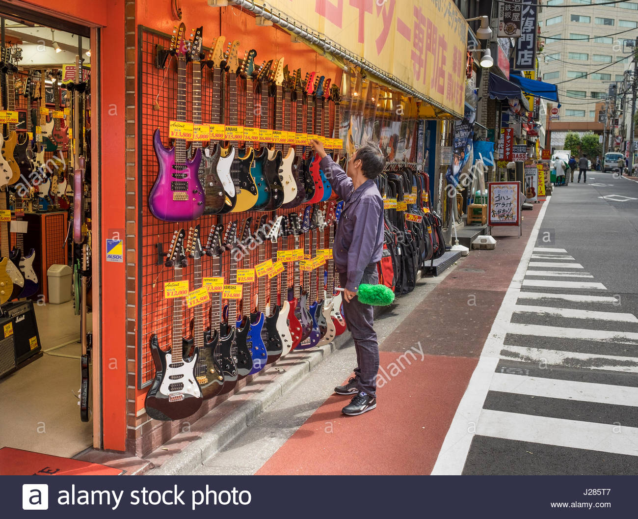 Man Adjusting Price Tags On Electric Guitars Display Outside Music Shop Off Meidai Dori Knows As Guitar Street A Musical Instrument Shopping Stre
