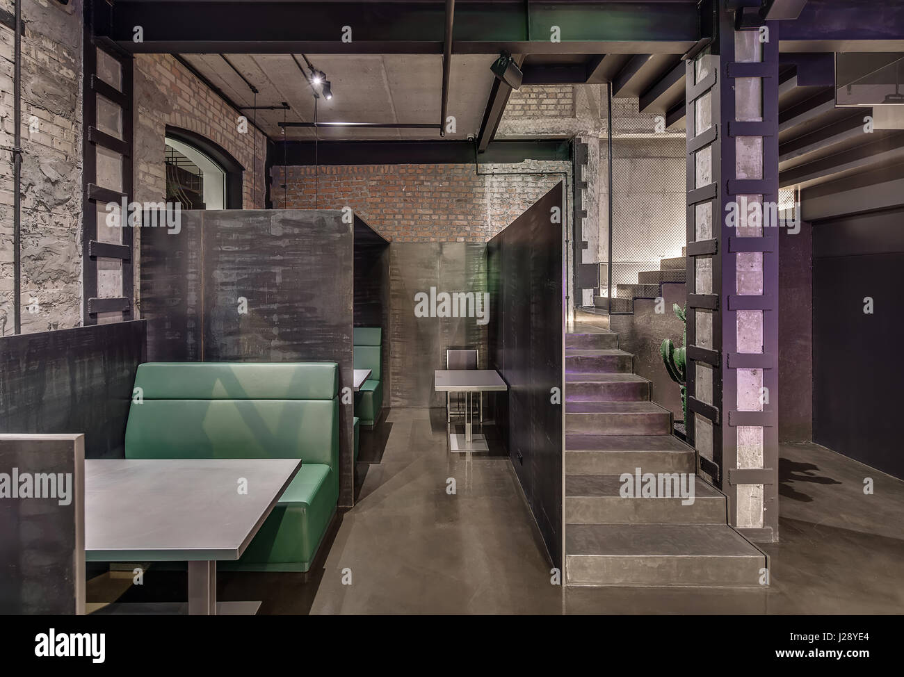 loft style cafe with brick and concrete walls column stairway with reticulated partition and glowing lamps there are green sofas with gray tables a - Concrete Cafe Interior