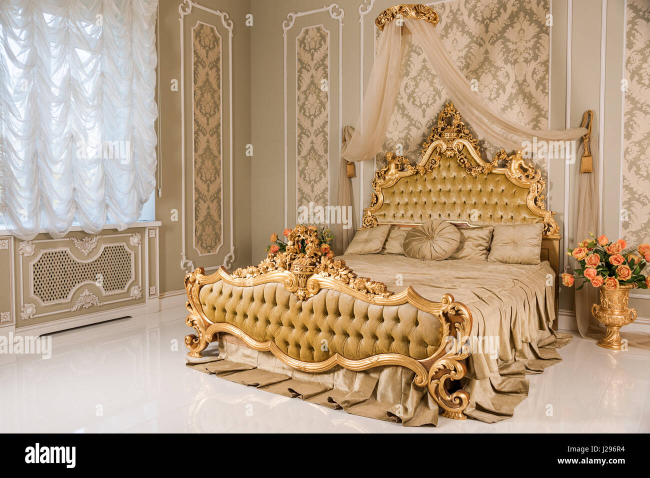 Luxury bedroom in light colors with golden furniture details. Big ...