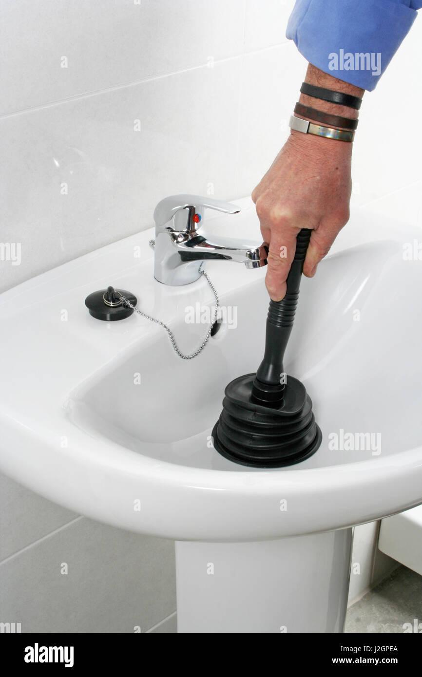 Unclogging A Bathroom Sink Handyman Unclogging Bathroom Sink With A Plunger Stock Photo