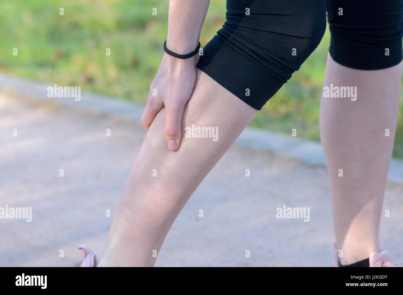 Young woman jogger suffering from calf muscle spasm or cramps ...
