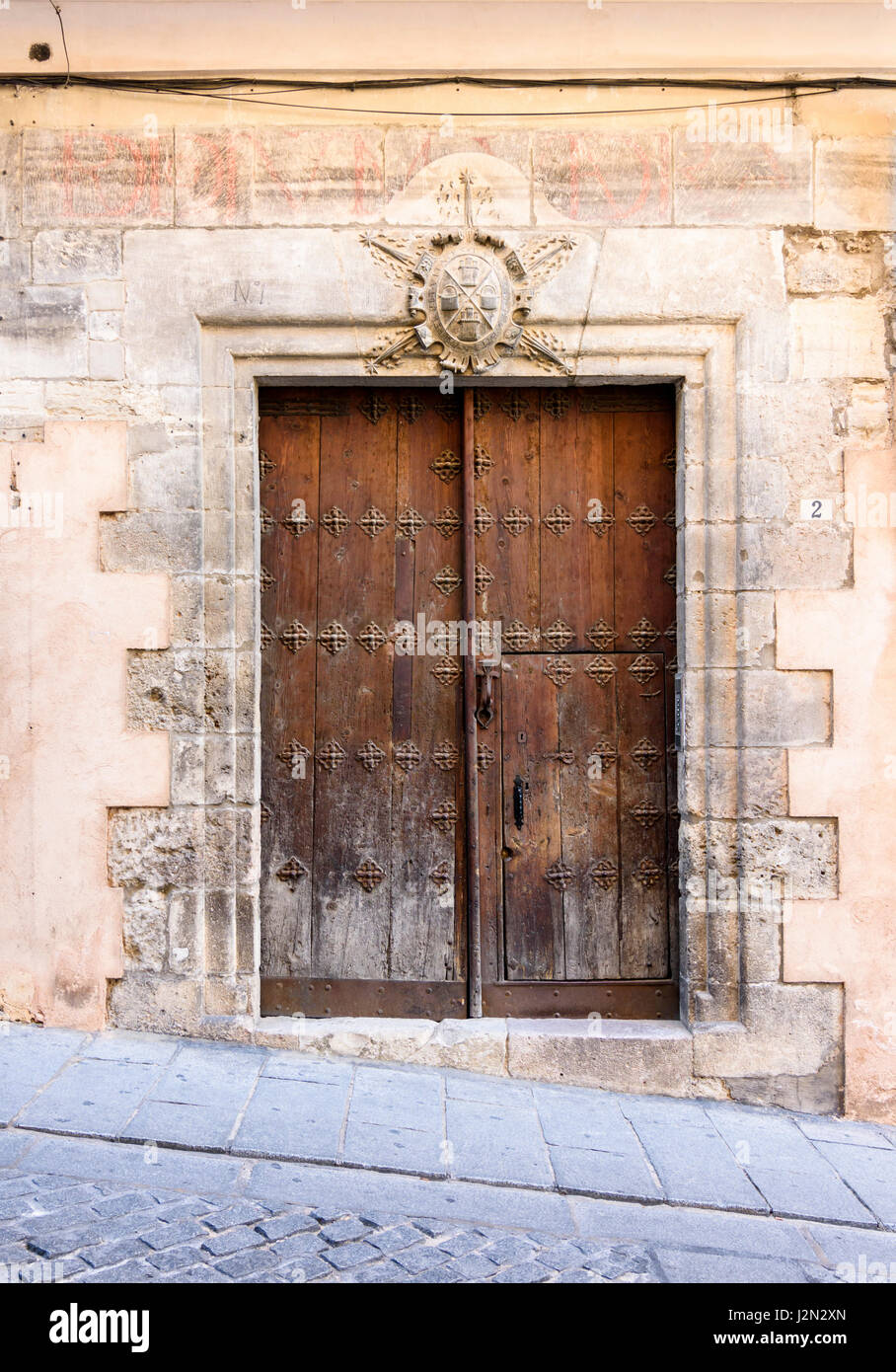 Old Wooden Double Doors Below A Coat Of Arms On A Historic Building In The  Old Medieval Town Of Cuenca, Castilla La Mancha, Spain