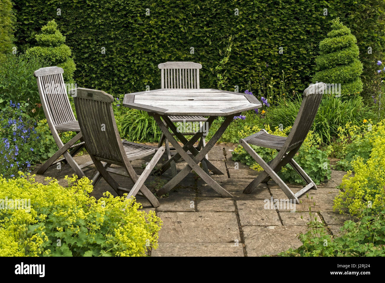 Wooden table and four chairs on small slabbed garden patio for Small patio table and 4 chairs