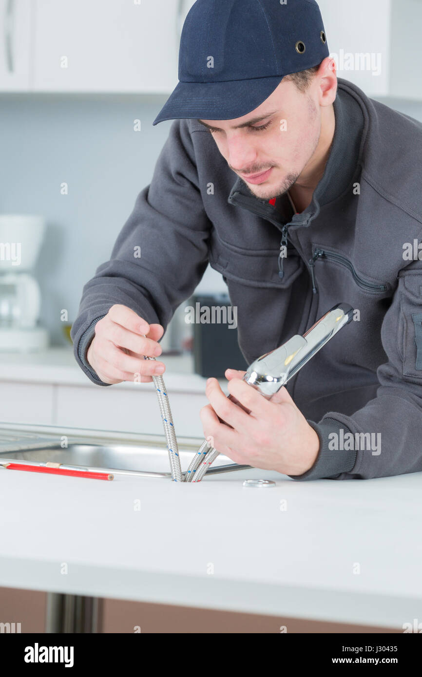 plumber fixing water tap in kitchen Stock Photo, Royalty Free Image ...