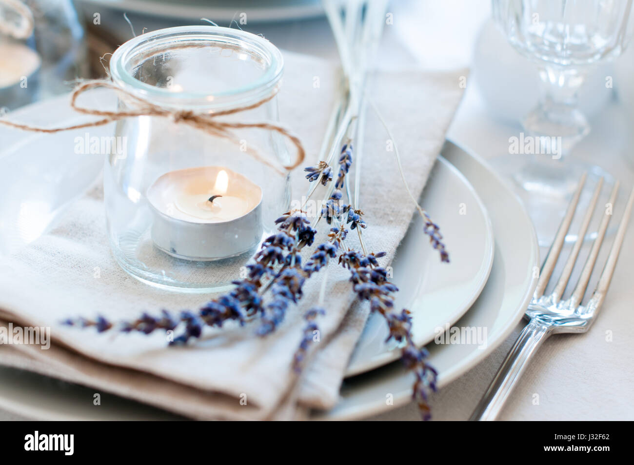 Dining table setting at Provence style with candles lavender vintage crockery and cutlery closeup & Dining table setting at Provence style with candles lavender ...