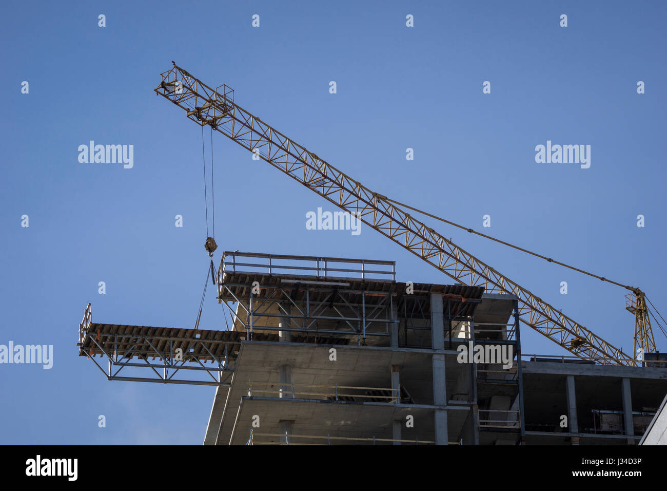 Tower crane moves a flying form used to support concrete pours in ...