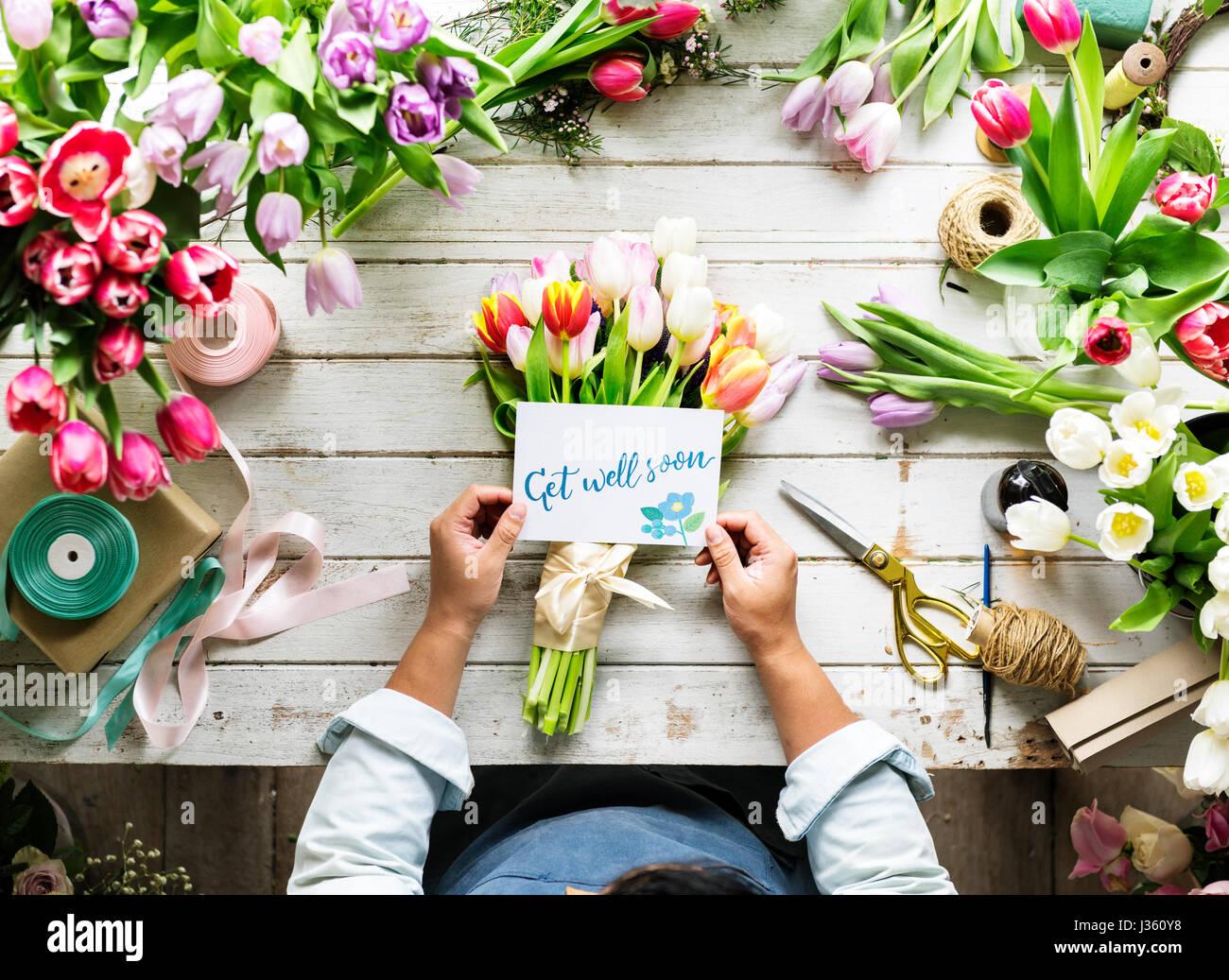 Florist making fresh flowers bouquet arrangement with get well florist making fresh flowers bouquet arrangement with get well soon wishing card dhlflorist Images