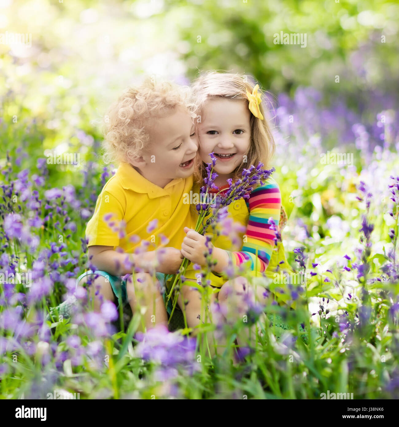 kids with bluebell flowers boy and girl gardening children play outdoor in bluebells meadow