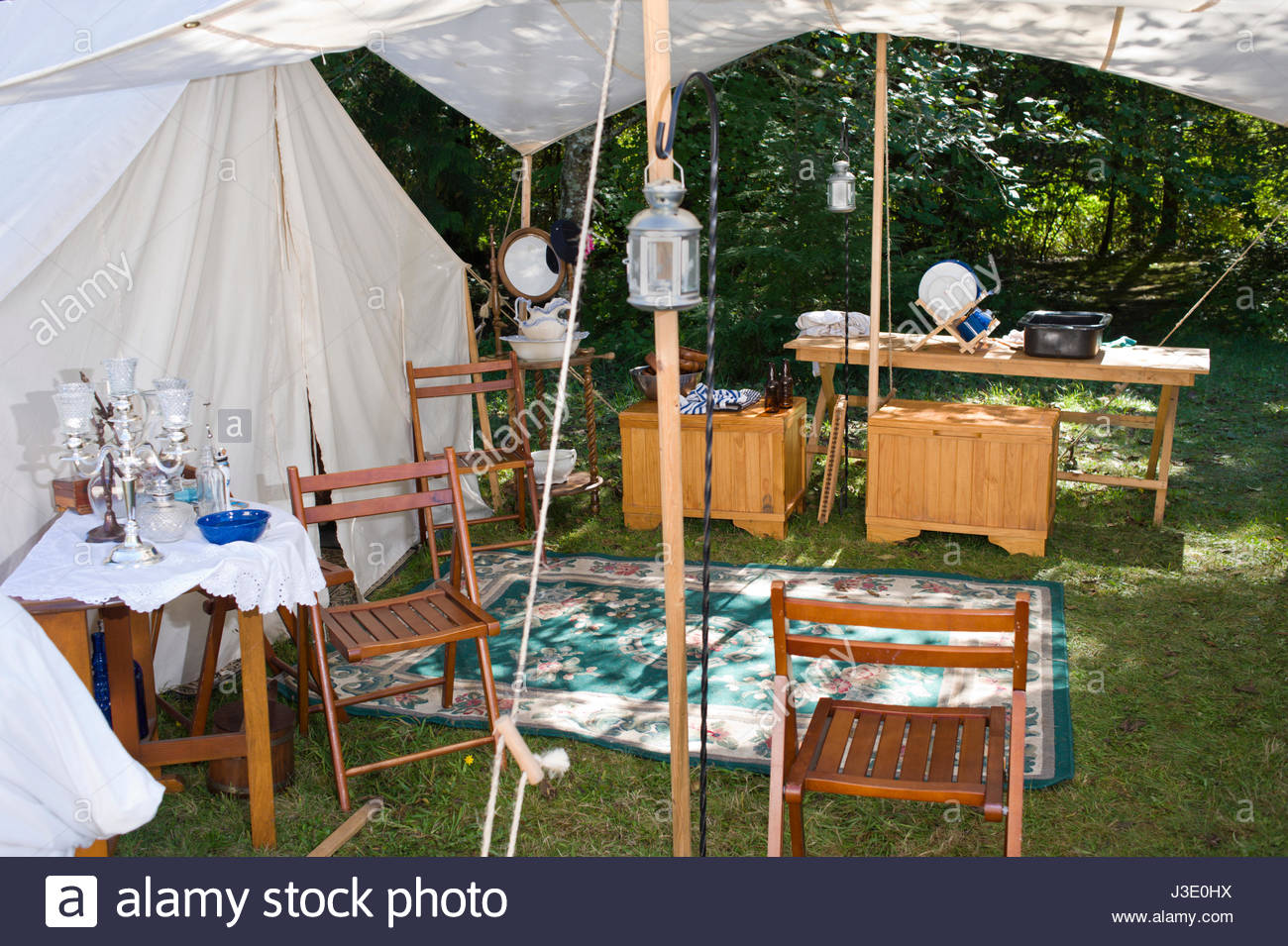 white canvas tents and awning with wood camp furniture and