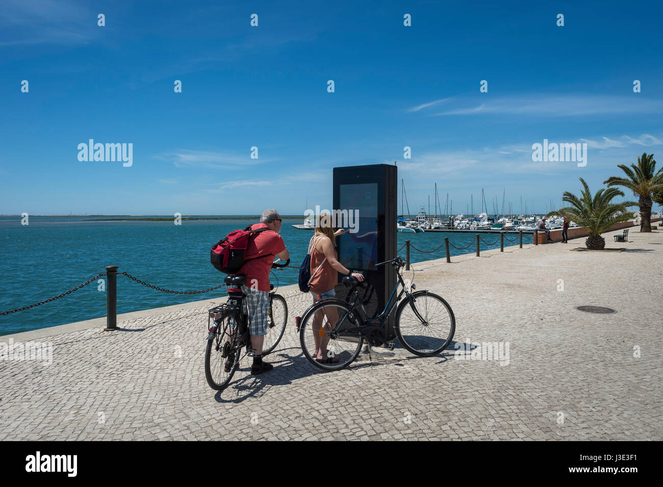 Couple Of Tourists On Bicycles Using An Interactive Tourist Map In - Portugal map interactive