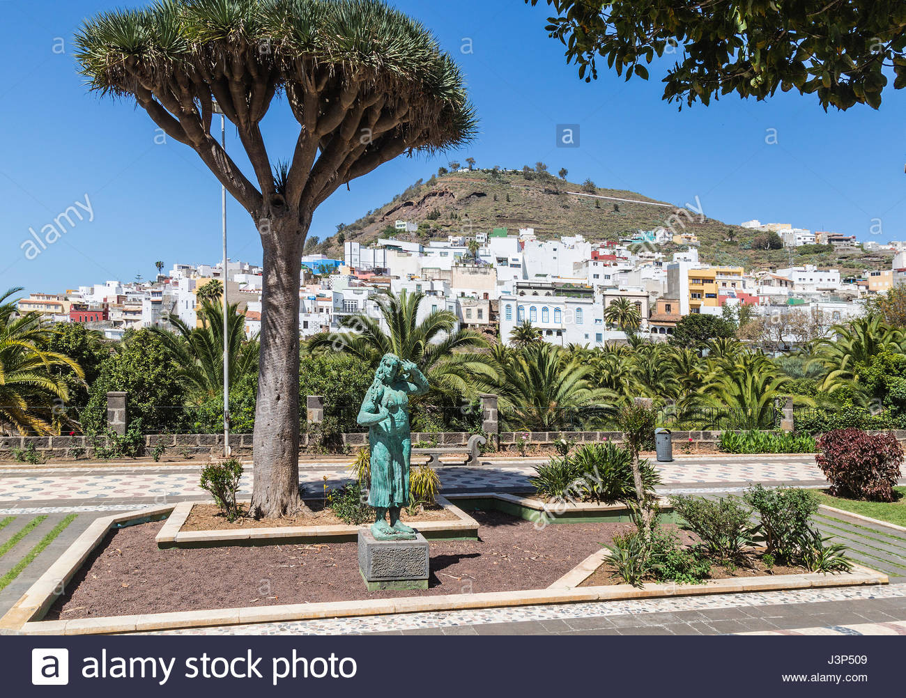 Statue In The Municipal Gardens At Arucas On Gran Canaria, One Of The  Canary Islands, With The Town Houses On The Hillside In The Background