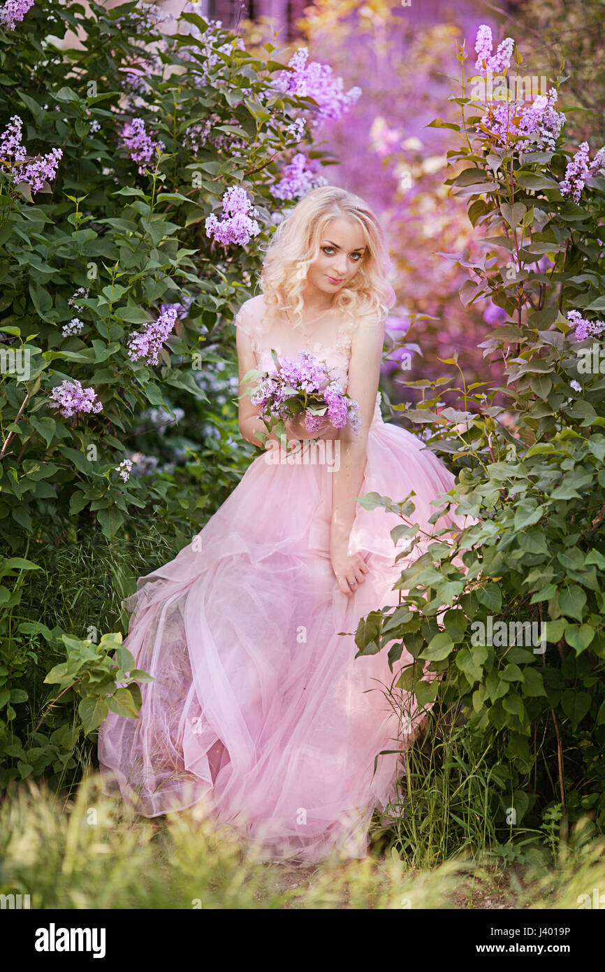 Beautiful woman enjoying lilac garden young woman with flowers in beautiful woman enjoying lilac garden young woman with flowers in green park cheerful teenager walking outdoor soft light style color izmirmasajfo Image collections