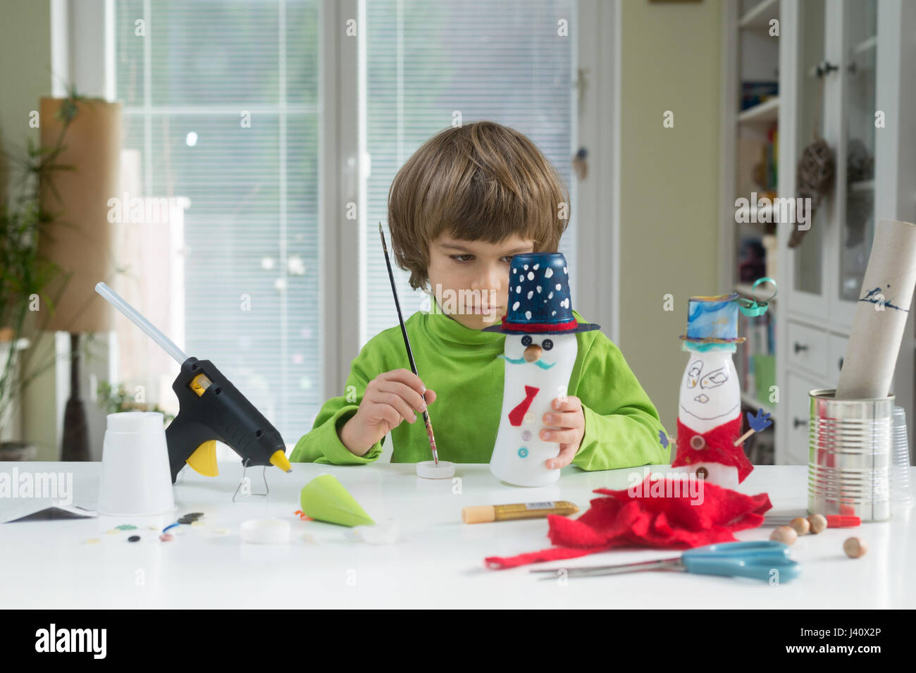Little boy being creative making homemade do it yourself toys out of little boy being creative making homemade do it yourself toys out of yogurt bottle and paper supporting creativity learning by doing hand craft cr solutioingenieria Images