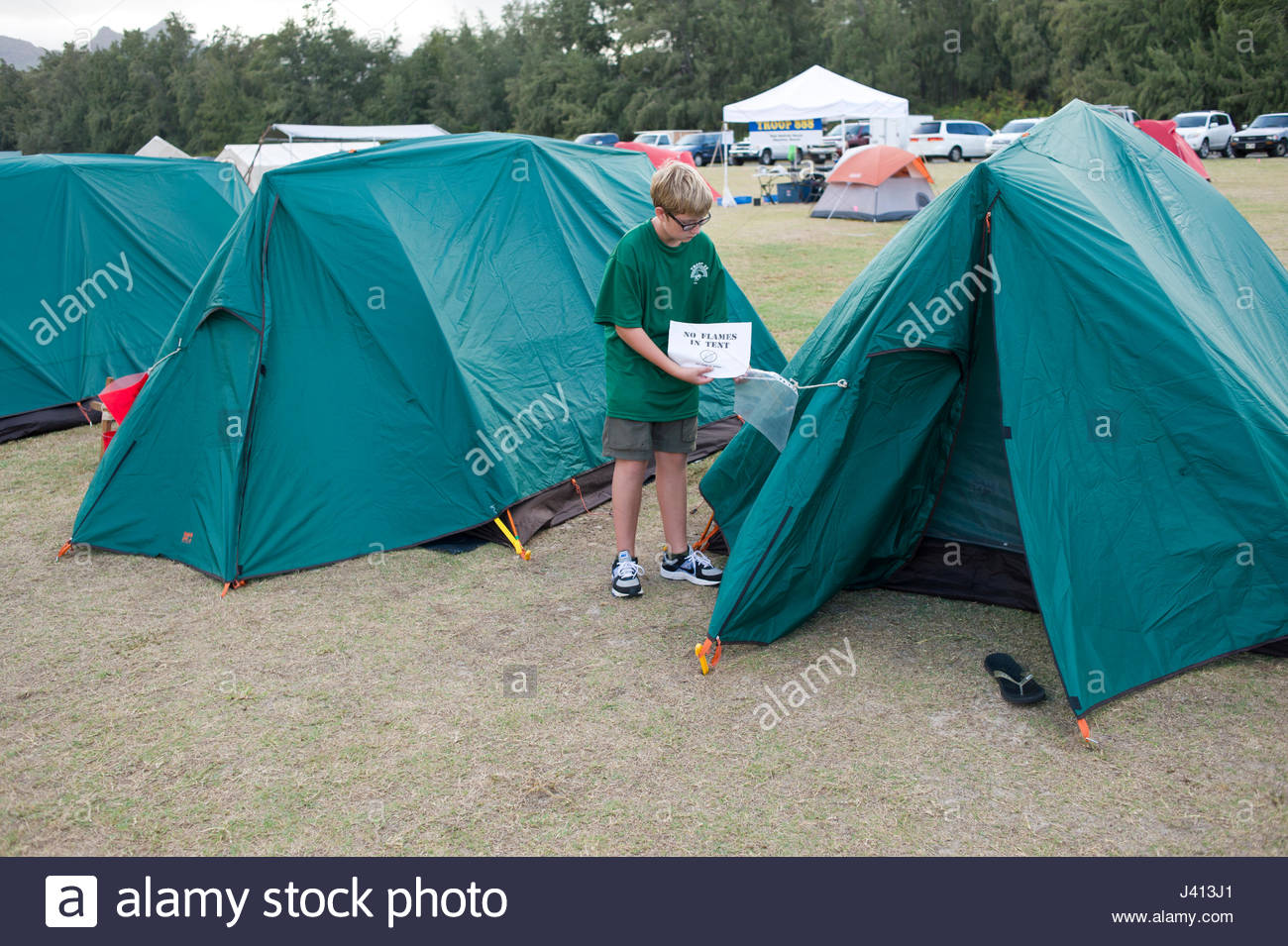 Young Caucasian teenage male fixing warning sign onto green tent during a Boy Scout c& at Bellows Air Force Station Waimanalo Oahu Hawaii USA & Young Caucasian teenage male fixing warning sign onto green tent ...