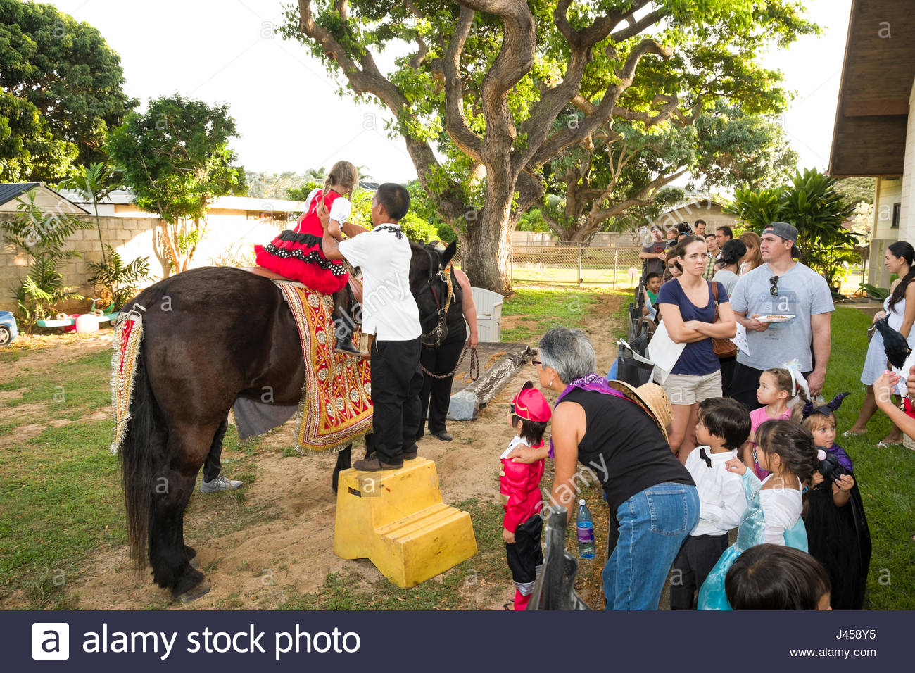 Man helping young girl onto a horse during a Halloween party Stock ...