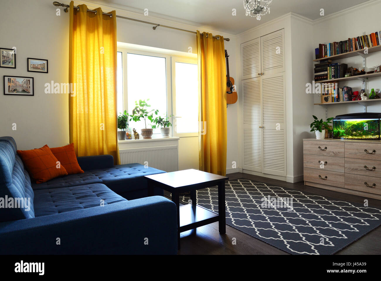 Clean family room with blue couch, white brick wall and yellow ...