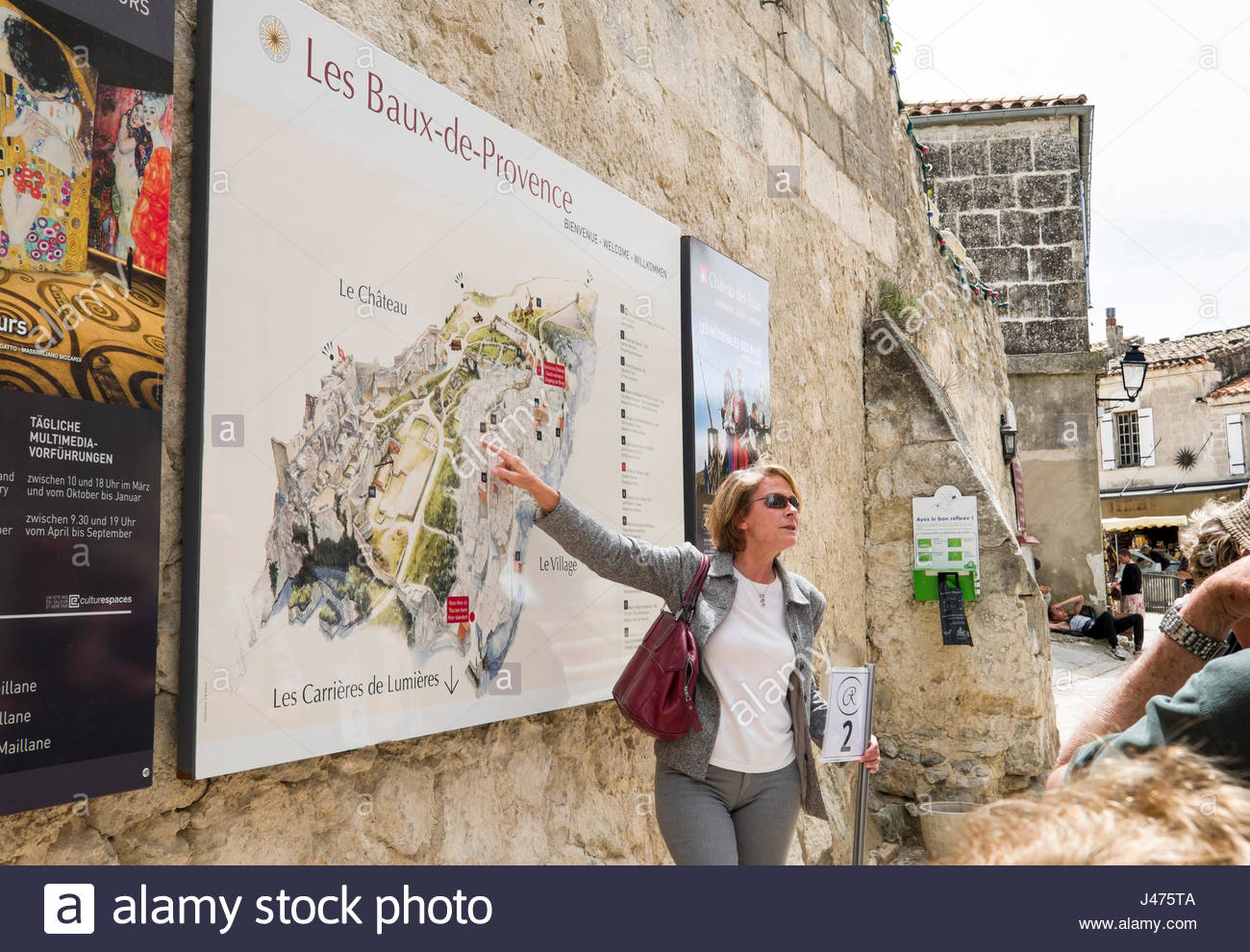 Female tour guide point to map of Les BauxdeProvence Arles Stock
