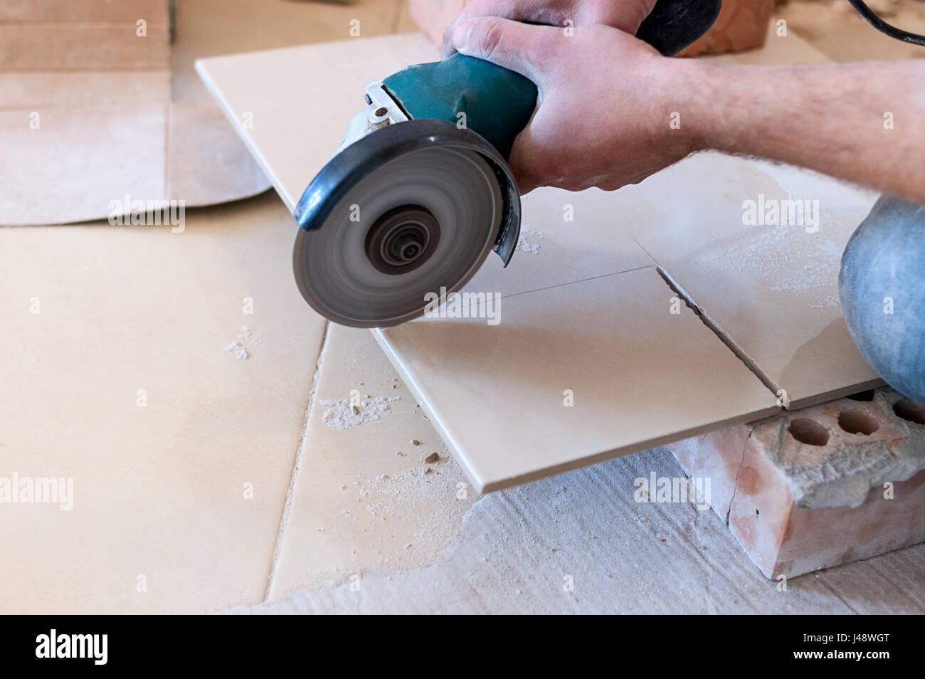 A construction worker cutting a tile using an angle grinder stock a construction worker cutting a tile using an angle grinder dailygadgetfo Choice Image