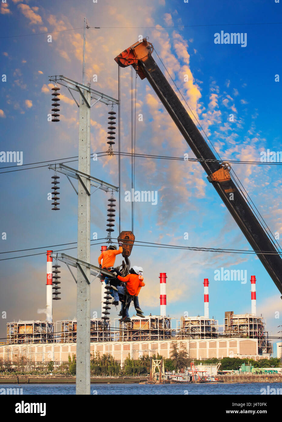 Stock Photo   Electrician Worker Working On High Voltage Electric Pole With  Crane Against Factory Building Background