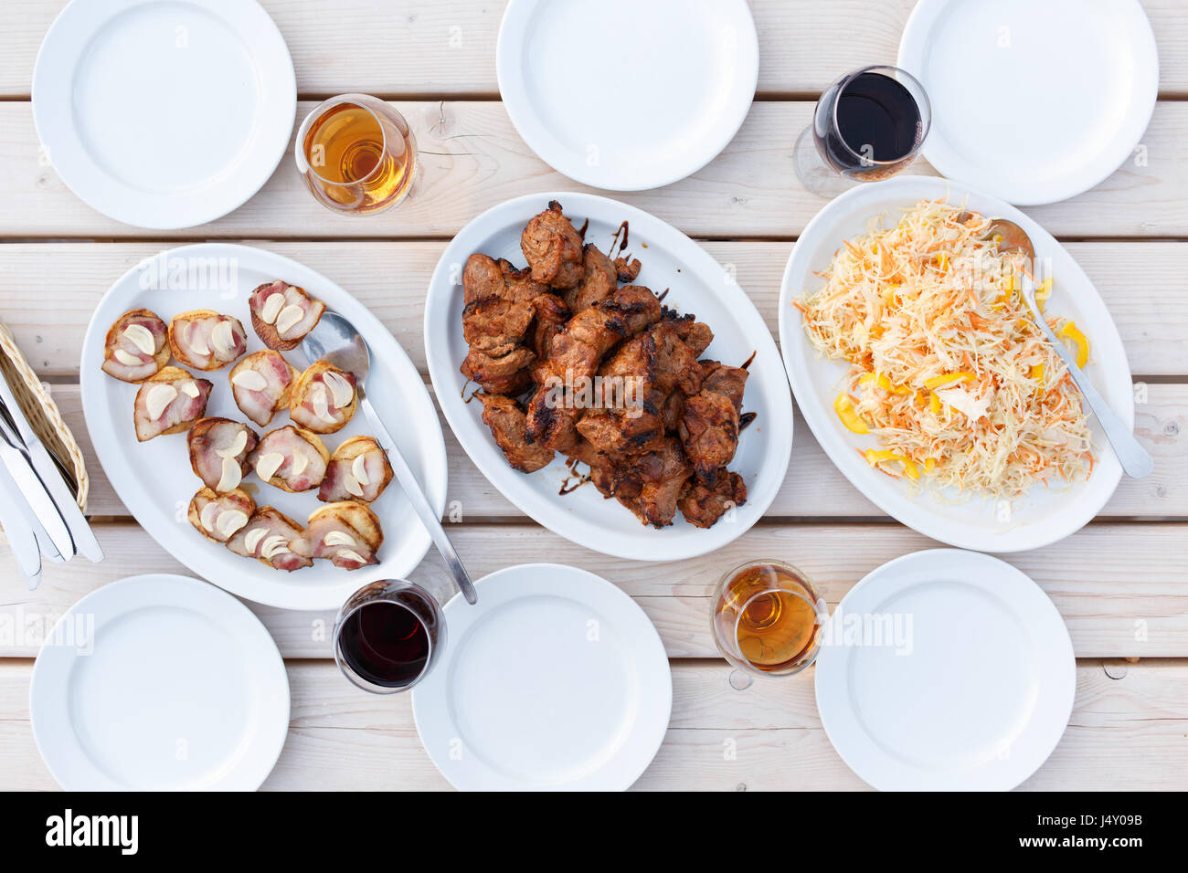 Dinner table top view - Stock Photo Top View Of Dinner Table With Shish Kebab Salad And Roasted Potatoes With Bacon Served Table With Barbecue Meat And Empty Dishes