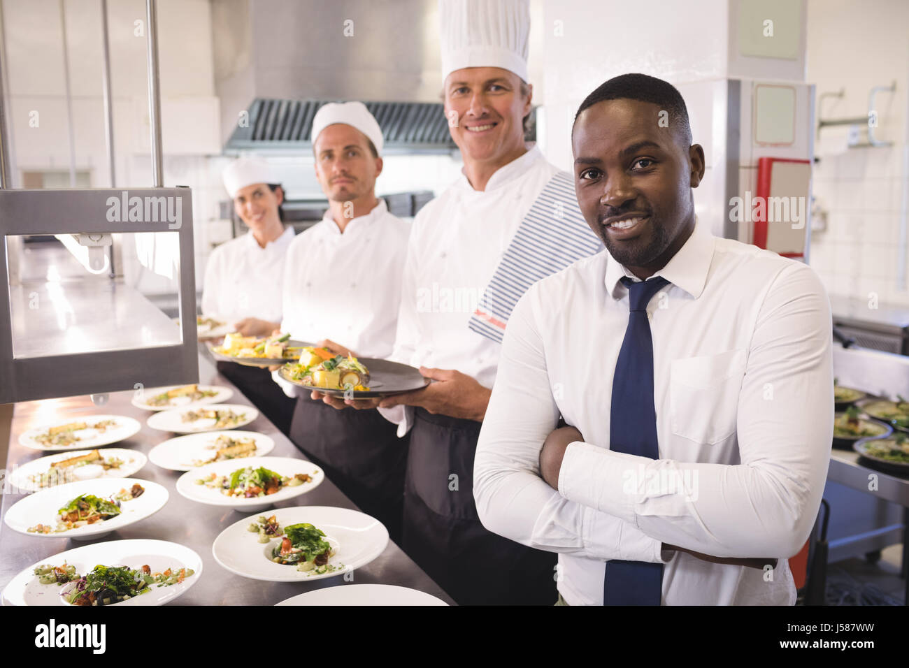 Restaurant Kitchen Staff smiling black chef standing arms stock photos & smiling black chef