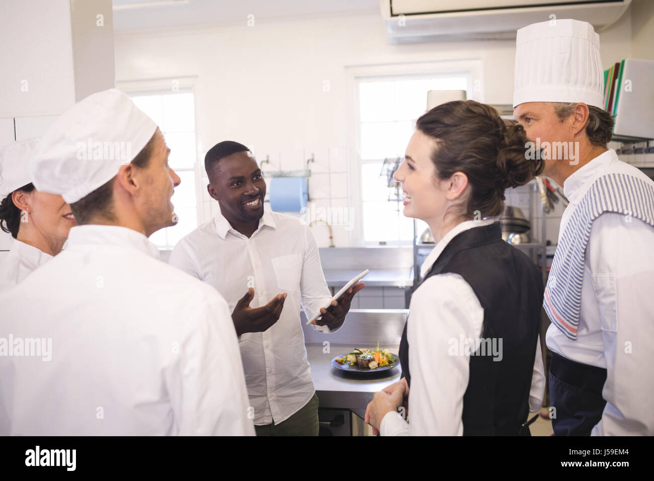 Restaurant Kitchen Staff male restaurant manager briefing to his kitchen staff in the stock