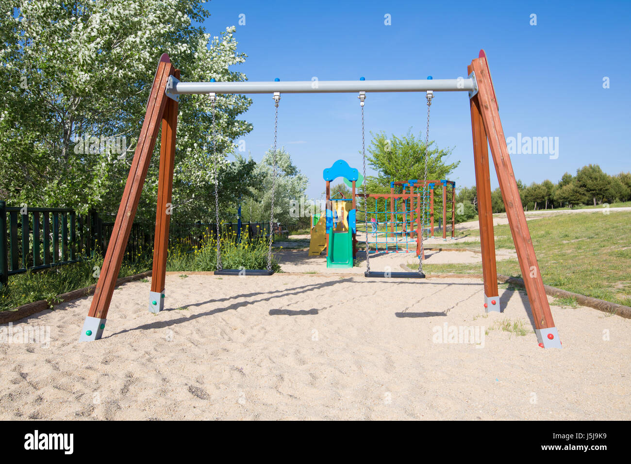 Plastic Two Swing Sets On Earth Sand Ground In Playground With Slide Stock Photo Royalty Free